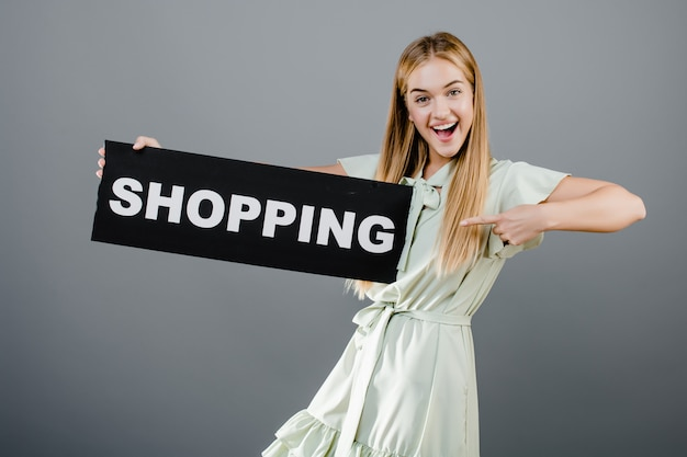 Happy smiling beautiful blonde girl with shopping sign isolated