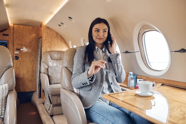 Счастливая улыбающаяся красивая деловая женщина в частном самолете