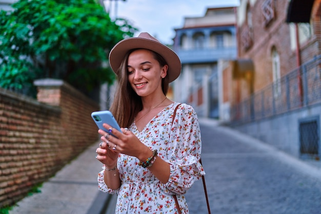 Happy smiling beautiful cute joyful young girl traveler using smartphone during vacation weekend time while sightseeing