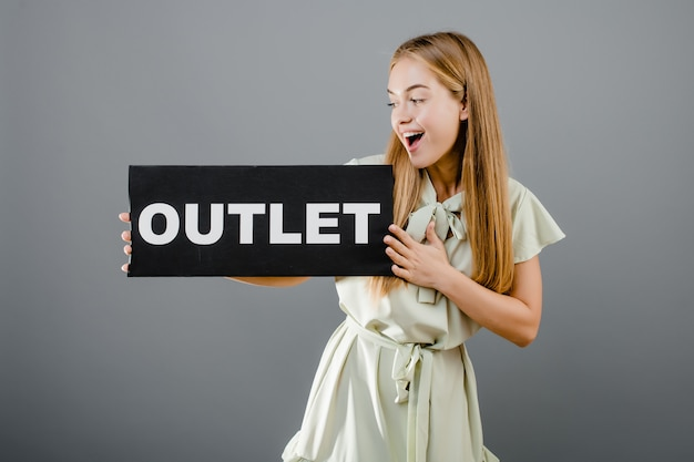 Happy smiling beautiful  woman with outlet sign isolated over grey