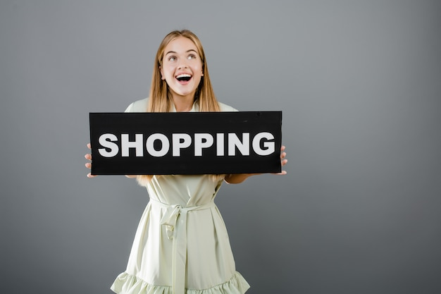 Happy smiling beautiful woman with shopping sign isolated over grey