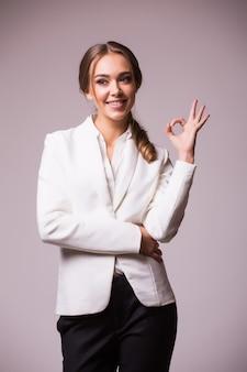 Bella giovane donna di affari sorridente felice che mostra gesto giusto, sul muro grigio. modello biondo caucasico nel concetto di presentazione aziendale. composizione quadrata.