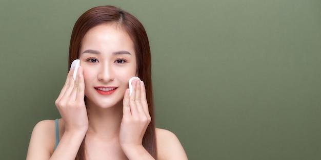 Счастливая улыбающаяся красивая молодая женщина, чистящая кожу ватным диском.