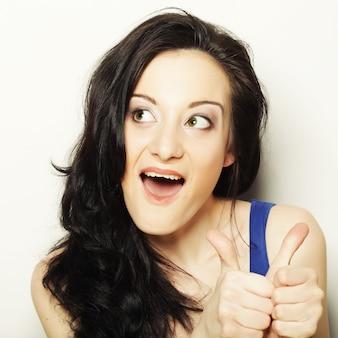 Счастливая улыбающаяся красивая молодая женщина показывает палец вверх жестом