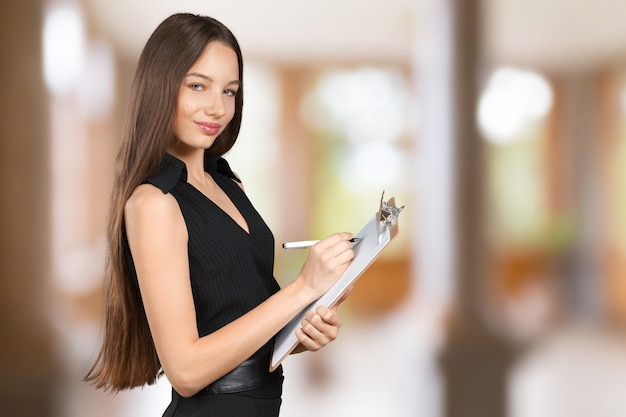 Happy smiling beautiful young woman with clipboard