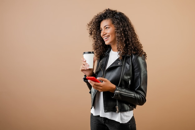 Happy smiling black girl with phone and coffee to go cup isolated over brown