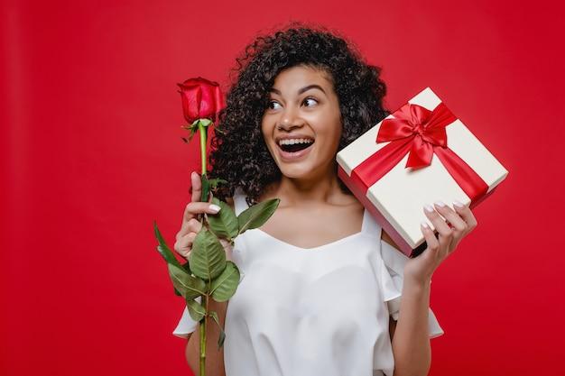 ローズとギフトボックスが赤で分離された幸せな笑みを浮かべて黒少女