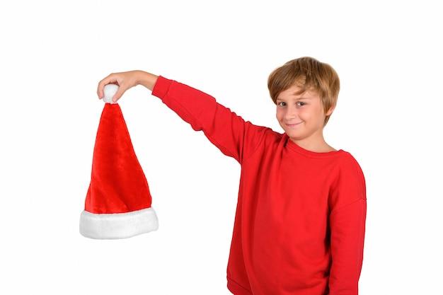 Счастливый улыбающийся белокурый мальчик в красном пуловере, держащий и показывающий шляпу санта-клауса