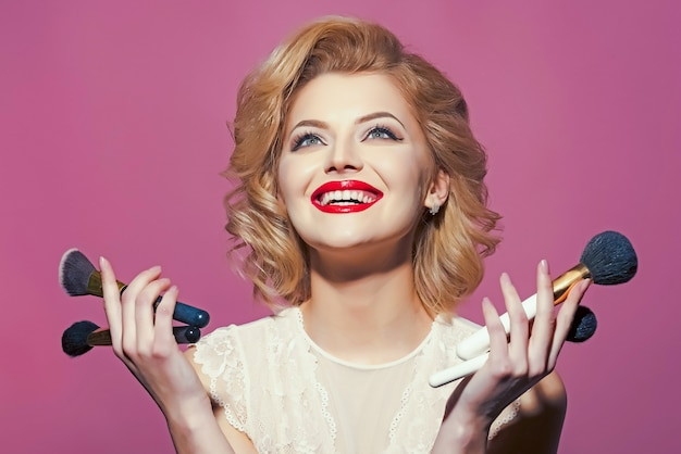 Счастливая улыбающаяся белокурая девушка с элегантным ретро макияжем, кинозвездой.