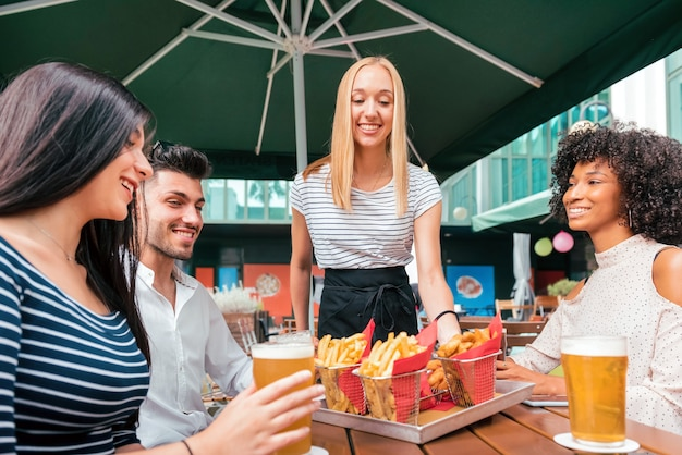 Happy smiling blond waitress serving fried potato chips at a pub table to a group of diverse young friends enjoying a cold beer together