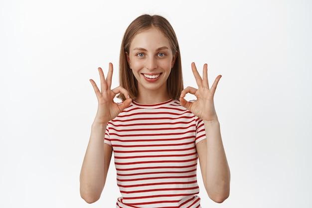 Счастливая улыбающаяся белокурая женщина дает ей гарантию, показывая «окей», «окей», без жестов и одобрительно кивая, заверяя, что все под контролем, хвалят отличный результат, рекомендуя что-л.