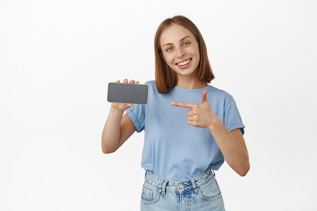 La donna bionda sorridente felice presenta l'app, puntando il dito sullo schermo orizzontale dello smartphone e sembra soddisfatta, consigliando la funzione del telefono cellulare, il negozio di esposizione, il muro bianco