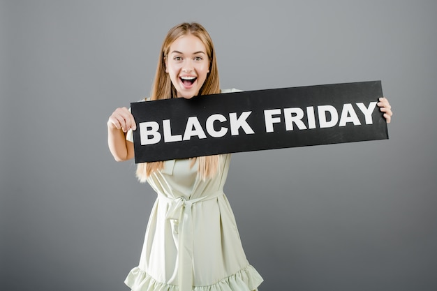 Happy smiling blonde girl with black friday sign isolated over grey