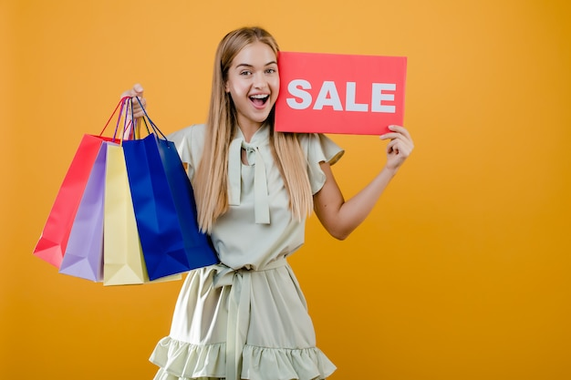Happy smiling blonde girl with sale sign and colorful shopping bags isolated over yellow