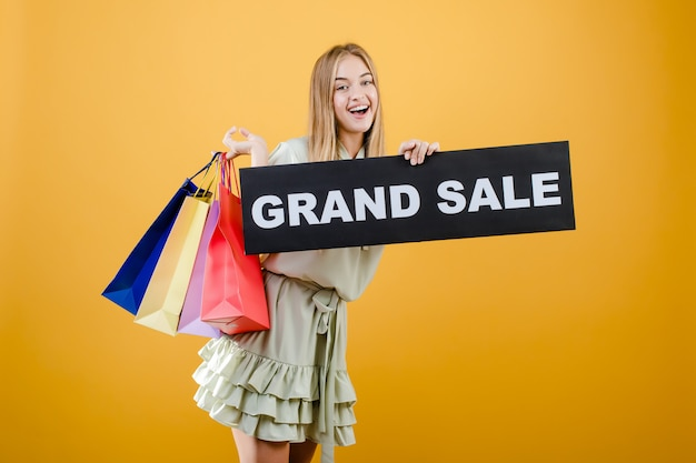 Happy smiling blonde woman has grand sale sign with colorful shopping bags isolated over yellow