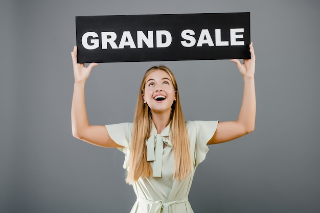 Happy smiling blonde woman with grand sale sign isolated
