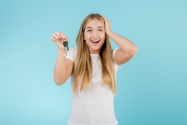 Happy smiling blonde woman with keys from apartment isolated over blue