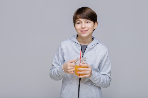 Happy smiling boy drinking fresh juice from glass with a straw