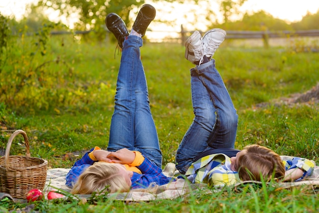 Happy smiling boy and girl lying together on the grass