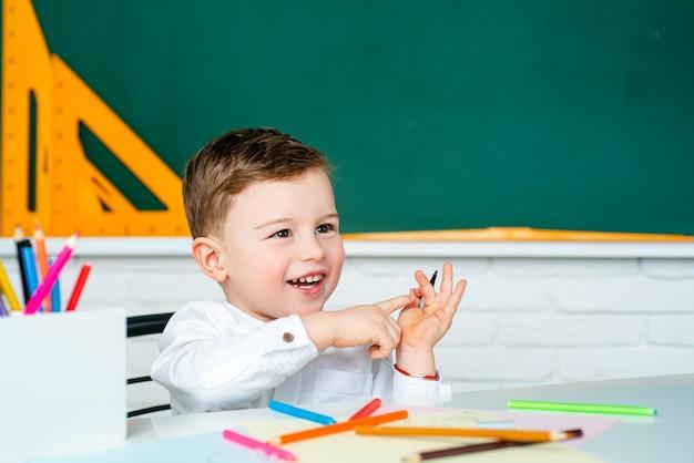 初めて学校に行く幸せな笑顔の少年。黒板に対して楽しんでいる陽気な笑顔の小さな男の子。学校に戻る。