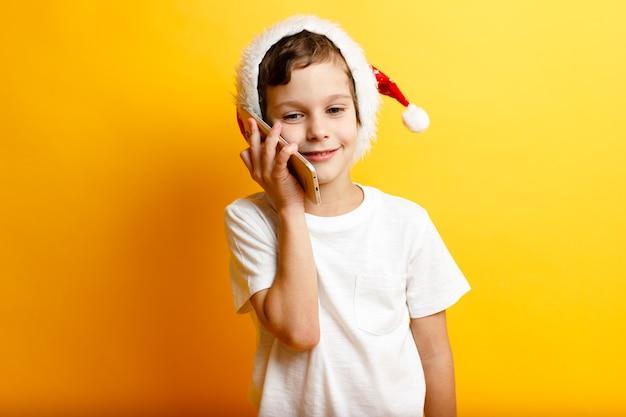 Счастливый улыбающийся мальчик в красной рождественской шляпе с телефоном на желтом