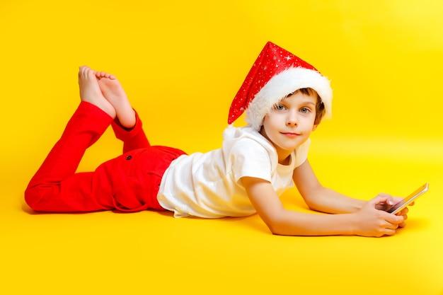 Счастливый улыбающийся мальчик в красной шляпе рождество с телефоном