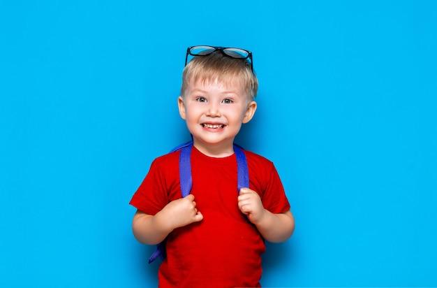 彼の頭の上に眼鏡をかけて赤いtシャツで幸せな微笑む少年は初めて学校に行きます。ランドセルを持つ子供。キッド