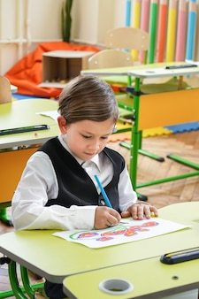 Счастливый улыбающийся мальчик рисует и впервые идет в школу. ребенок с школьной сумкой и книгой. малыш в помещении класса с доской на фоне. обратно в школу.