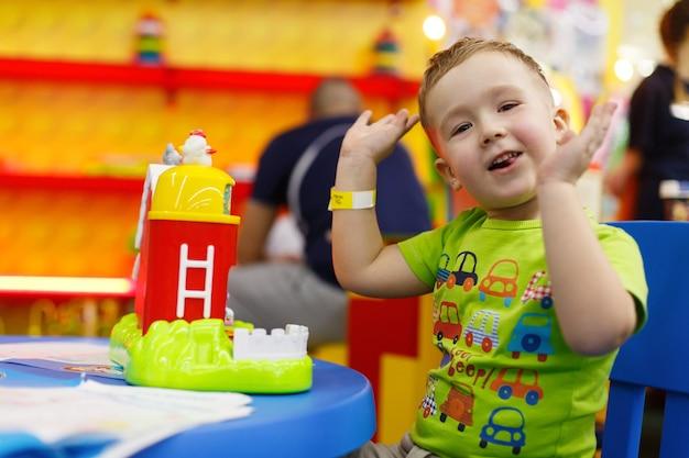 Счастливый улыбающийся мальчик играет с красочной игрушкой в детской комнате милый ребенок в детском саду