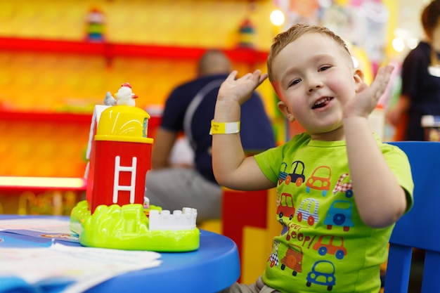 Happy smiling boy is playing with a colorful toy in children room cute child in kindergarten