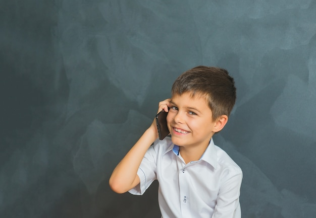 Happy smiling boy in a white shirt talking on phone, little boss.