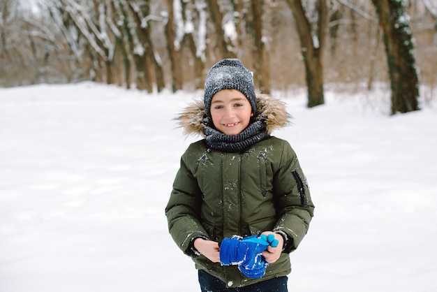 Happy smiling boy in winter clothes during walk