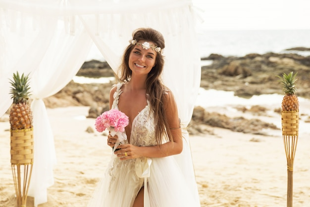 Happy smiling bride in beautiful wedding dress on the beach