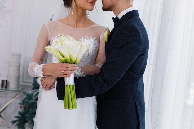 暗いスーツのブライダルブーケと新郎と幸せな笑顔の花嫁は美しい結婚式のカップルをクローズアップ
