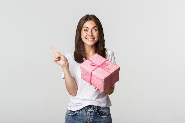 Счастливая улыбающаяся брюнетка девушка держит подарок на день рождения и показывает пальцем влево на логотип