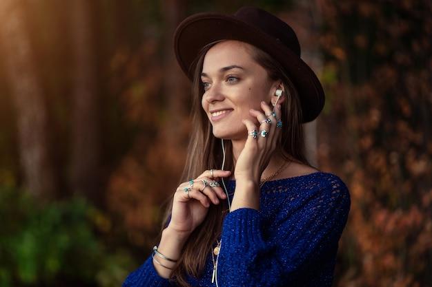 Счастливая улыбающаяся брюнетка в коричневой шляпе и в вязаном свитере в серебряных кольцах с бирюзовым камнем с удовольствием слушает осеннюю музыку в наушниках на улице осенью