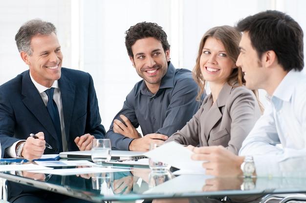 幸せな笑顔のビジネス人々を議論し、オフィスで一緒に働いて