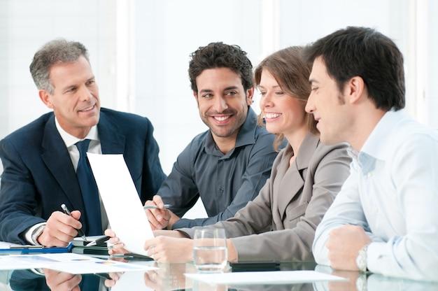 オフィスで一緒に働いて幸せな笑みを浮かべて事業チーム