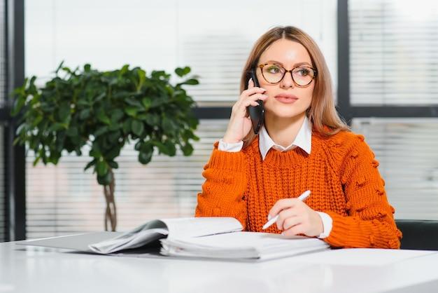 電話で話し、オフィスの彼女の職場に座って、コピースペースで仕事で幸せな笑顔のビジネス女性