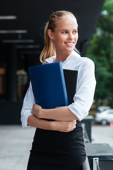 Happy smiling business woman holding folders while standing outdoors
