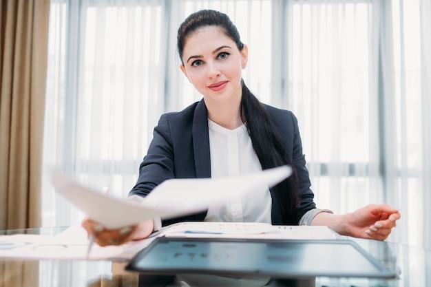 Счастливая улыбающаяся деловая женщина в офисном рабочем пространстве
