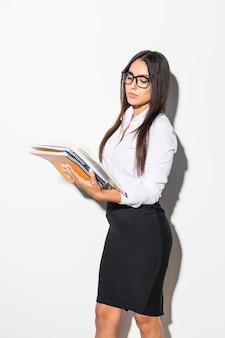 Donna o studente sorridente felice di affari in vestiti eleganti che tengono taccuino e penna su bianco