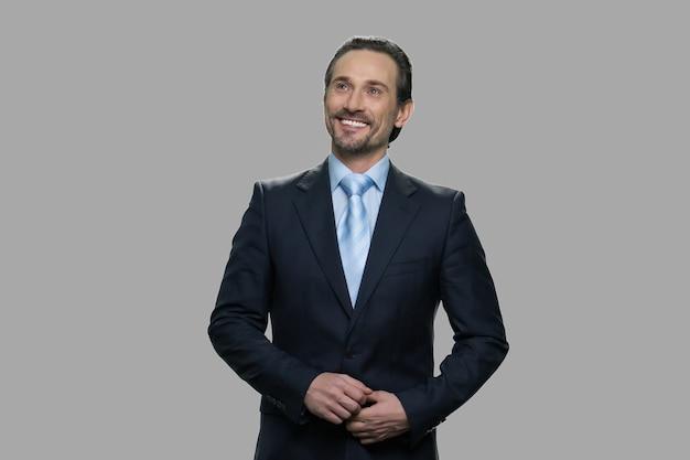 灰色の背景に空想の幸せな笑顔の実業家。見上げる幸せな思いやりのあるビジネスマンの肖像画。