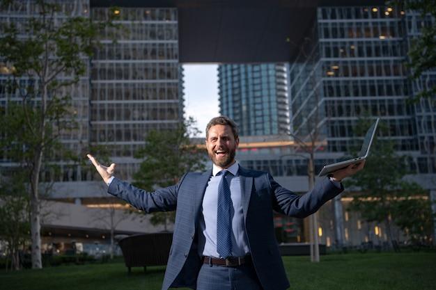 近くに立っている間取引をするためにオフィスの成功した雇用主の近くでスーツを着た幸せな笑顔のビジネスマン...
