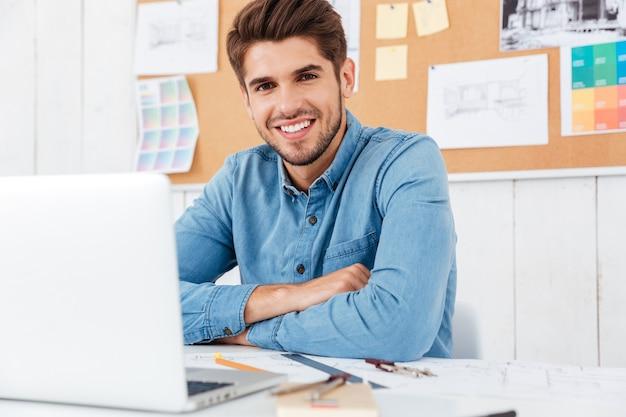 Счастливый улыбающийся бизнесмен, сидящий за столом со скрещенными руками в офисе
