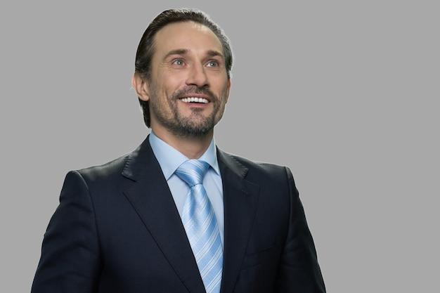 思いやりのある表情で幸せな笑顔のビジネスマン。灰色の背景に魅力的な空想のビジネスパーソン。将来の成功を夢見ています。