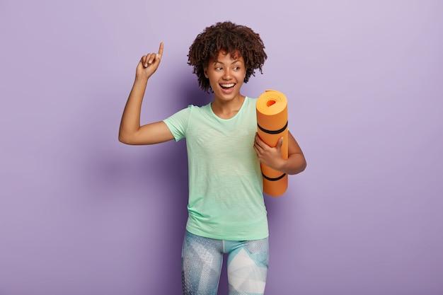 행복하게 웃는 평온한 곱슬 머리 아프리카 계 미국인 운동가는 구겨진 요가 매트를 들고 팔을 들고 위쪽을 가리키며 좋은 훈련을 즐기고 티셔츠와 레깅스를 입습니다. 스포츠 컨셉