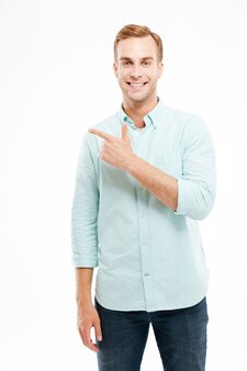 Счастливый улыбающийся случайный мужчина, указывая пальцем в сторону copyspace, изолированного на белой стене