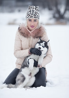 Happy smiling caucasian blonde woman and her husky dog. playing outdoors in winter white forest together.