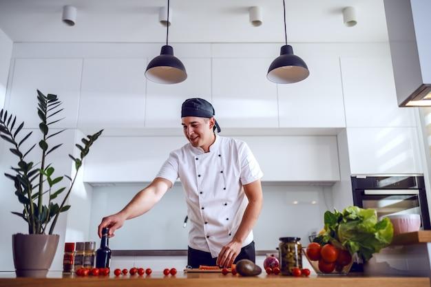 Happy smiling caucasian chef in uniform standing in domestic kitchen and preparing salmon.